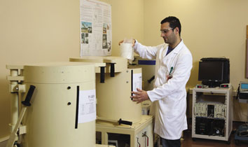 ARPANSA radiochemist placing a food sample into the Germanium Gamma Ray spectrometer to measure radioactivity.
