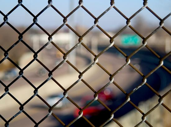 Close up of fence with traffic on freeway out of focus in the background.